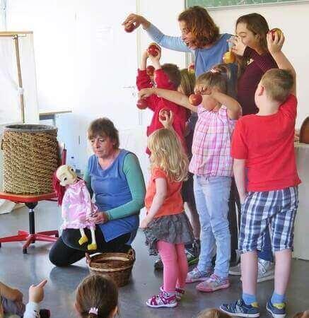 előadás, gyerekek almákat tartanak