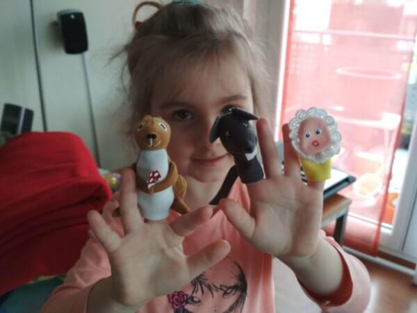 kislány bábokkal az ujjain