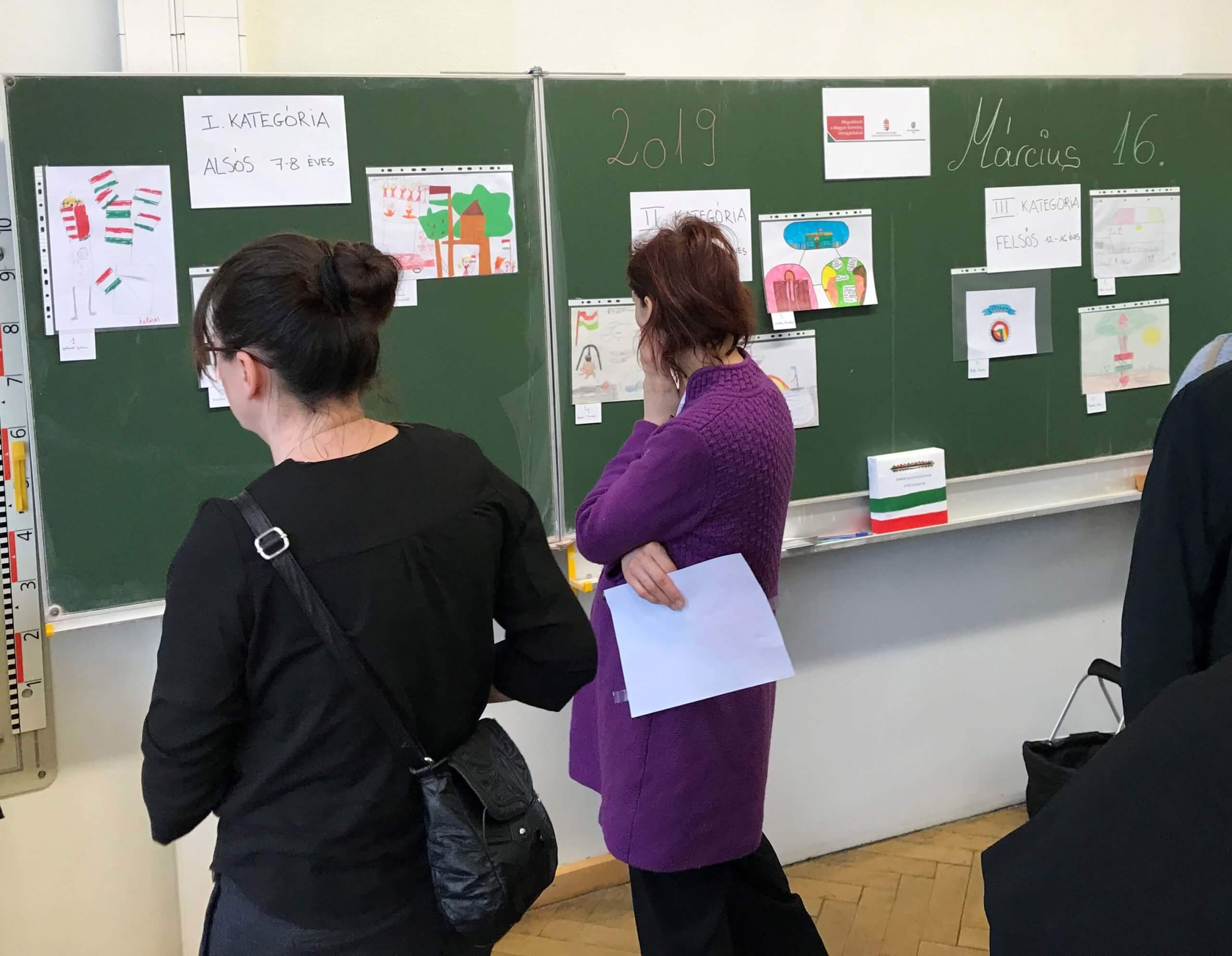 felnőttek nézik a rajzpályázat munkáit