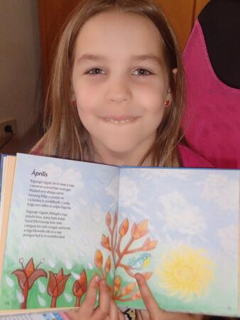 egy kislany egy könyvvel a kezében